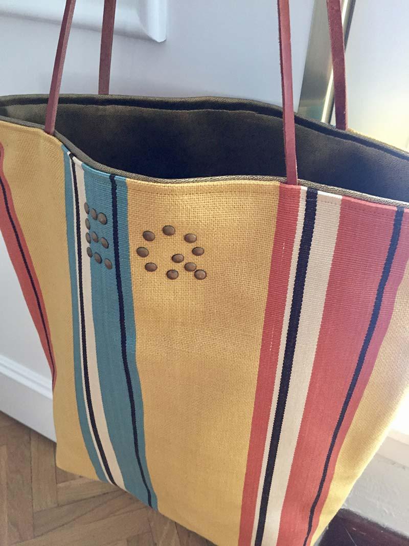 Bolsa con las letras EQ puestas con tachuelas.